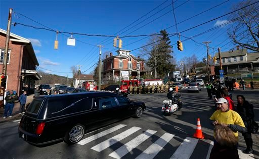 In this Dec. 19, 2012, file photo, firefighters and others line up as a hearse travels through the Sandy Hook village of Newtown, Conn., during a procession toward St. Rose of Lima parish cemetery.