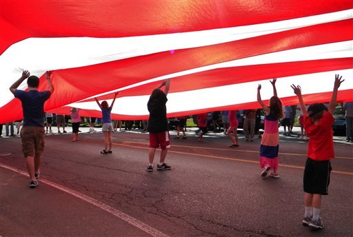 In this Oct. 9, 2011, file photo, children hold a flag as it passes down Main Street during the annual Labor Day parade in Newtown, Conn.