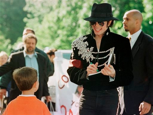 In this May 28, 1997 file photo, U.S. entertainer Michael Jackson gives a little boy an autograph upon his arrival in the northern town of Bremen, where he will begin his Germany concert tour on May 31.