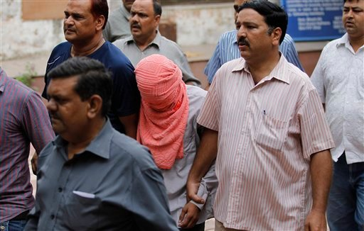Delhi police officers escort a juvenile accused of rape, outside the Juvenile justice board in New Delhi, India, Saturday, Aug. 31, 2013.