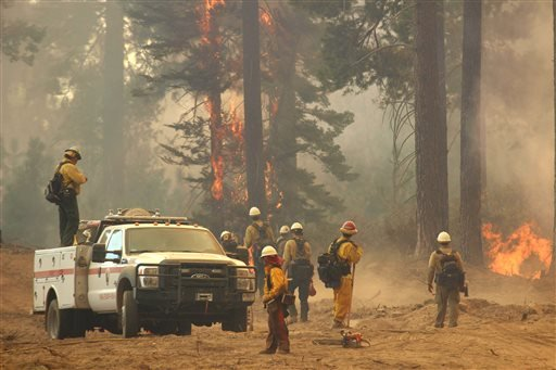 In this Friday, Aug. 30, 2013 photo provided by the U.S. Forest Service, a fire crew stands watch along a fire break near a burn operation on the southern flank of the Rim Fire near Yosemite National Park in California.