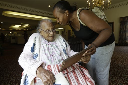 In this Tuesday, July 30, 2013 photo, Jacquelin Finley, right, shows her grandmother Ida Filey, 101, a family photo she recovered during a visit to the house she grew up in with her grandmother in Dirgin, Texas.