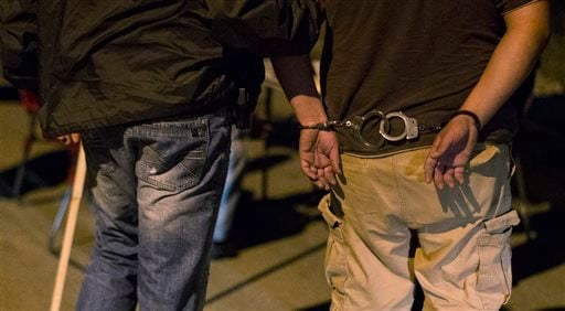 "A ""john"" who attempted to pick up an officer posing as a prostitute is escorted in handcuffs to an area where he will be ticketed during a prostitution sting in Cicero, Ill., Thursday, Aug. 15, 2013."