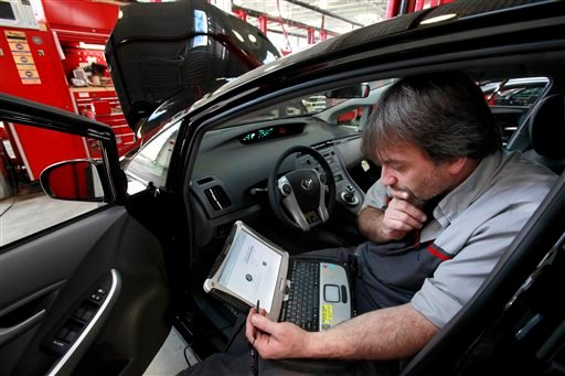 In this Feb. 9, 2010 file photo, master diagnostic technician Kurt Juergens, of Foxborough, Mass., uses a laptop computer to diagnose and repair the brake system on a 2010 Toyota Prius in the repair shop of a Toyota dealership, in Norwood, Mass.
