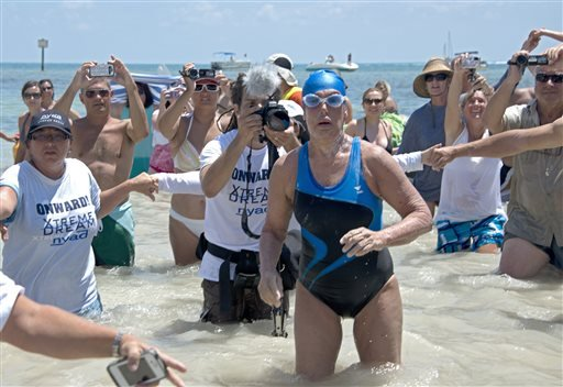 In this photo provided by the Florida Keys News Bureau Diana Nyad emerges from the Atlantic Ocean after completing a 111-mile swim from Cuba to Key West, Fla. Nyad, 64, is the first swimmer to cross the Florida Straits without the security of a shark cage