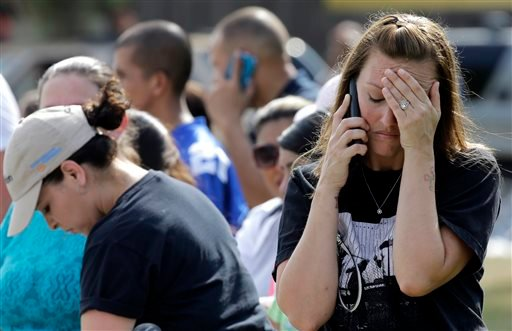 Laurie Garza talks on the phone as she waits for her daughter outside Spring High School Wednesday, Sept. 4, 2013, in Spring, Texas. (AP)