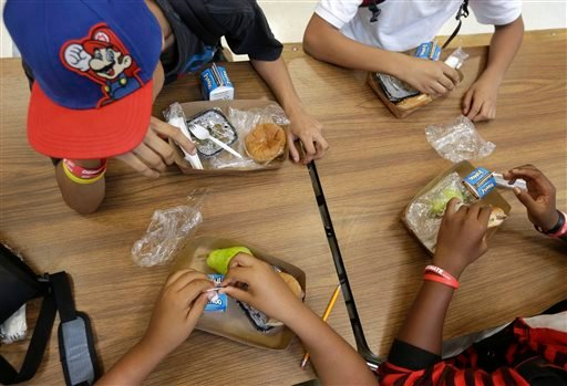 In this Sept. 4, 2013, photo, students at the Maurice J. Tobin K-8 School in Boston's Roxbury neighborhood eat free lunches consisting of a sandwich with meat, a vegetable dish, a piece of fruit, and milk.