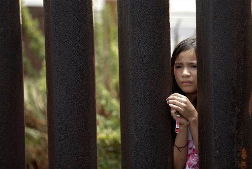 In this July 14, 2013 photo, Alondra Lopez, 8, looks through a fence between Tijuana, Mexico, where she stands, and San Diego, where her mother stands, during a cross-border Sunday religious service.
