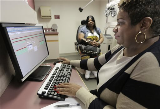 In this Sept. 5, 2013, Jacqueline Saulsberry, a service coordinator at the Illinois Eye Institute, gathers information from patient Shameka Lewis-Coolidge during an appointment in Chicago.