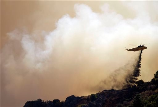 A helicopter drops retardant on a raging wildfire in Mount Diablo State Park in Contra Costa County, Calif. on Monday, Sept. 9, 2013. A wildfire burning outside Mount Diablo State Park has forced dozens of residents and animals to evacuate Monday.