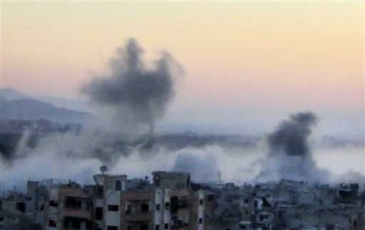 In this image taken from video obtained from the Shaam News Network, which has been authenticated based on its contents and other AP reporting, smoke rises from buildings due to heavy artillery shelling in Barzeh, a district of Damascus, Syria. (AP)