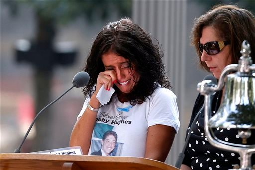 A woman wipes her eyes after reading the name of her brother, Bobby Hughes, as friends and relatives of the victims of the 9/11 terrorist attacks gather at the National September 11 Memorial. (AP Photo/Jason DeCrow)