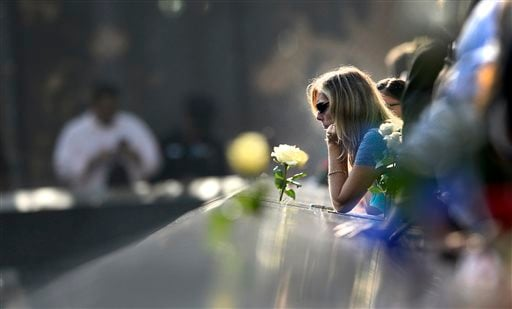 A woman pauses along the edge of the north reflecting pool at the 9/11 Memorial during a ceremony marking the 12th anniversary of the 9/11 attacks on the World Trade Center in New York, September 11, 2013. (AP Photo/ Justin Lane, Pool)