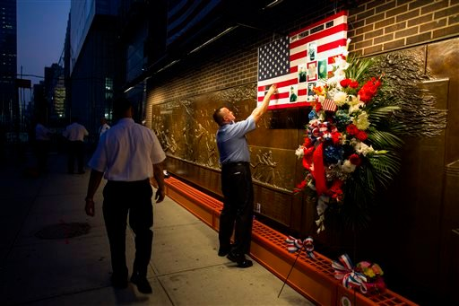 FDNY Firefighter Mike Bellantoni of New York prepares a memento at the Firefighter's Memorial adjacent to the World Trade Center Wednesday, Sept. 11, 2013 before the start of the official ceremonies at the 9/11 Memorial nearby. (AP Photo/Craig Ruttle)
