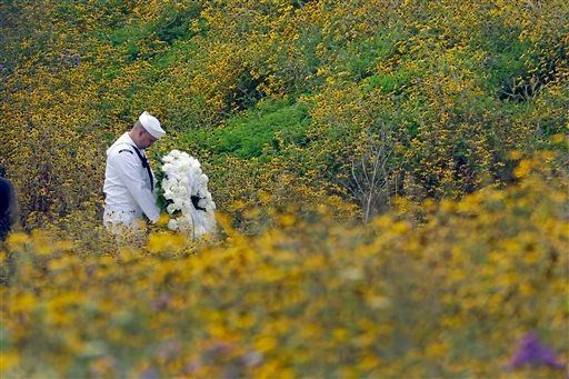 Navy Quartermaster Matthew Konchan of Johnstown, Pa., stands in a field of black-eyed Susan as he waits to participate in a wreath laying with Secretary of the Interior Sally Jewell during a memorial service at the Flight 93 National Memorial. (AP)