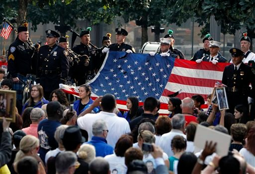 The World Trade Center Flag is presented as friends and relatives of the victims of the 9/11 terrorist attacks gather at the National September 11 Memorial at the World Trade Center site, Wednesday, Sept. 11, 2013. (AP)