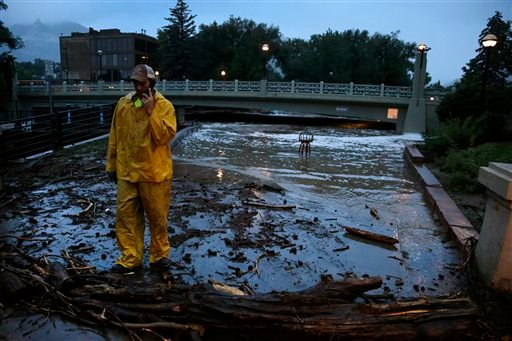 A city worker talks on his phone while surveying high water levels on Boulder Creek following overnight flash flooding in downtown Boulder, Colo., Thursday, Sept 12, 2013. (AP Photo/Brennan Linsley)