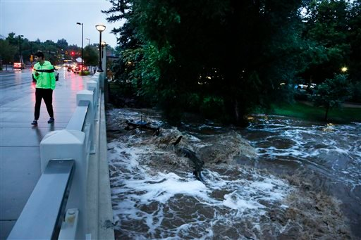 A man walks past dangerously high Boulder Creek following overnight flash flooding in downtown Boulder, Colo., Thursday, Sept 12, 2013.