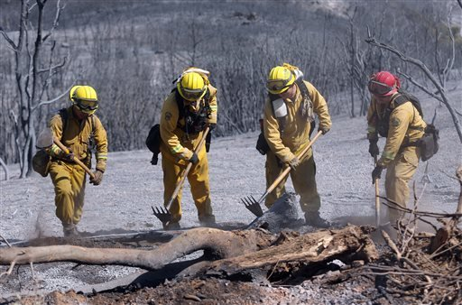 Marin County firefighters Jamal Cook, Miguel Palayo, Ryan Meier and Tony Soule, left to right, put out hot spots along a fire road near the north peak of Mount Diablo near Clayton, Calif. Sept. 10, 2013. (AP Photo/The Contra Costa Times, Jane Tyska)