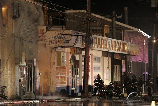 Firefighters battle a blaze in a building on the Seaside Park boardwalk on Thursday, Sept. 12, 2013, in Seaside Park, N.J. (AP Photo/Julio Cortez)