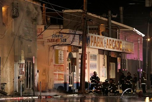 Firefighters battle a blaze in a building on the Seaside Park boardwalk on Thursday, Sept. 12, 2013, in Seaside Park, N.J. (AP Photo/Julio Cortez)