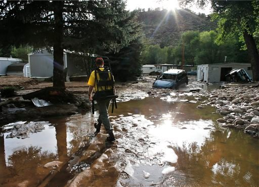 Local resident Ben Rodman walks while helping a friend salvage her home after floods left homes and infrastructure in a shambles, in Lyons, Colo., Friday Sept. 13, 2013.