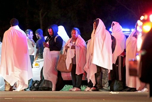 Passengers of an overturned Greyhound bus stand near the scene, Saturday, Sept. 14, 2013, on interstate I-75 in Liberty Township, Ohio. (AP Photo/Dayton Daily News, Nick Daggy)