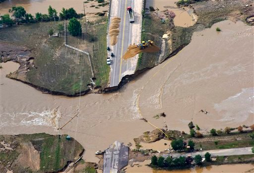 A road crew works on a stretch of highway washed out by flooding along the South Platte River in Weld County, Colorado near Greeley, Saturday, Sept. 14, 2013.