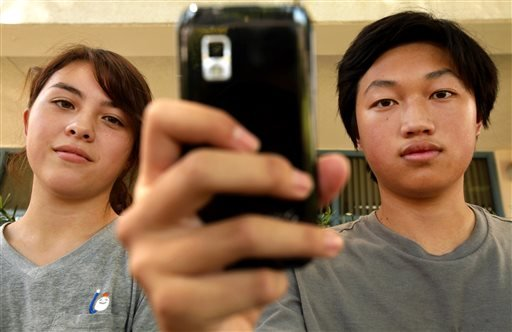 This Sept. 12, 2013, portrait of Young Cho, left, 16, and Christopher Chung, right,16, in front of their school Herbert Hoover High School in Glendale, Calif.