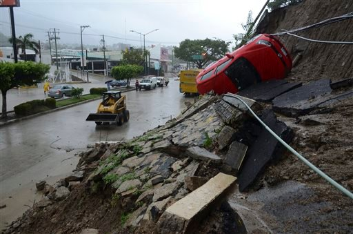 A car lies on its side after a portion of a hill collapsed due to heavy rains in the Pacific resort city of Acapulco, Mexico, Sunday, Sept. 15, 2013.