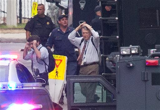 People hold their hands to their heads as they are escorted out of the building where a deadly shooting rampage occurred at the Washington Navy Yard in Washington, Monday, Sept. 16, 2013.(AP Photo/Jacquelyn Martin)