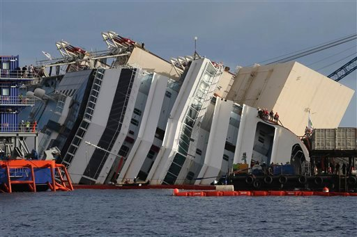 Workers watch the operations on the Costa Concordia ship, lying on its side on the Tuscan Island of Giglio, Italy, Monday, Sept. 16, 2013.