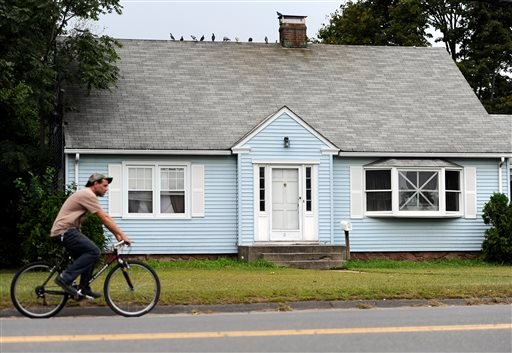 A man rides a bicycle by a house owned by the uncle of former New England Patriot's Aaron Hernandez, Thursday, Sept. 12, 2013 in Bristol, Conn.