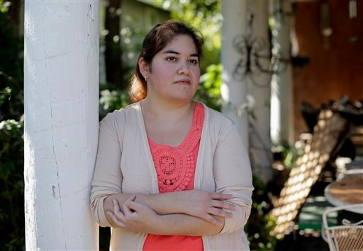 In this photo taken Friday, Sept. 13, 2013, Annette Guerra posses for a photo at her home in San Antonio. Guerra, 33, has been looking for a full-time job for more than a year after finishing nursing school.