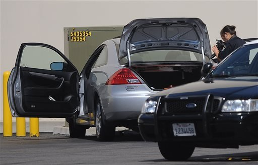 Crime scene investigators photograph a car believed to be driven by a women who allegedly tried to commit suicide by ramming it into a utility box behind a Costa Mesa shopping center.