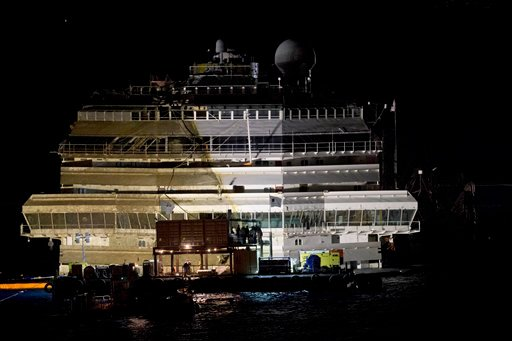 The Costa Concordia rests upright on the Tuscan Island of Giglio, Italy, early Tuesday morning, Sept. 17, 2013.