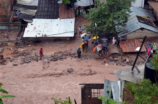 People stand next to damaged homes after a landslide caused by heavy rains came down on a low income neighborhood in the city of Chilpancingo, Mexico, Monday Sept. 16, 2013.