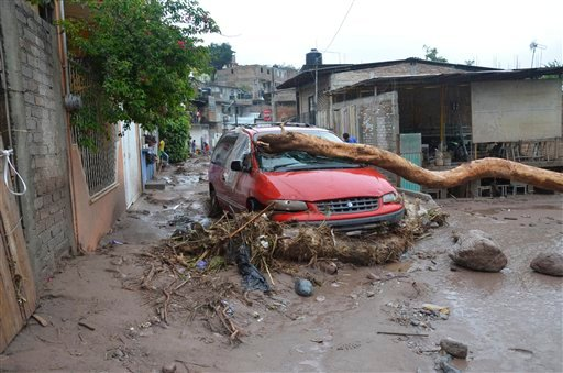 A damaged vehicle stands in the middle of a road after a landslide caused by heavy rains came down on a low income neighborhood in the city of Chilpancingo, Mexico, Monday Sept. 16, 2013.