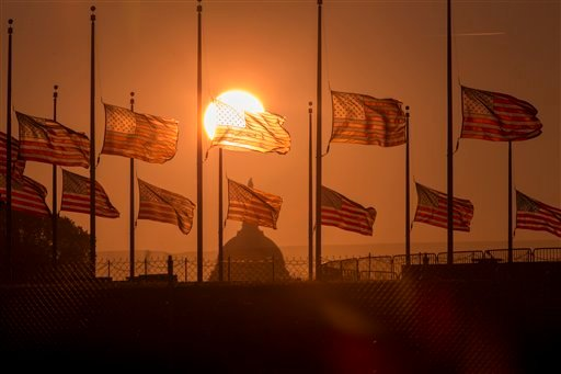 The American flags surrounding the Washington Monument fly at half-staff as ordered by President Barack Obama following the deadly shooting Monday at the Washington Navy Yard, Tuesday morning, Sept. 17, 2013, in Washington. (AP)