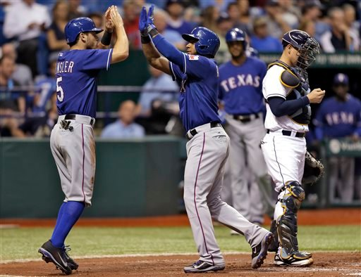 Texas Rangers' Elvis Andrus, center, high fives teammate Ian Kinsler, left, after Andrus hit a third-inning, two-run home run off Tampa Bay Rays starting pitcher Jeremy Hellickson. (AP)