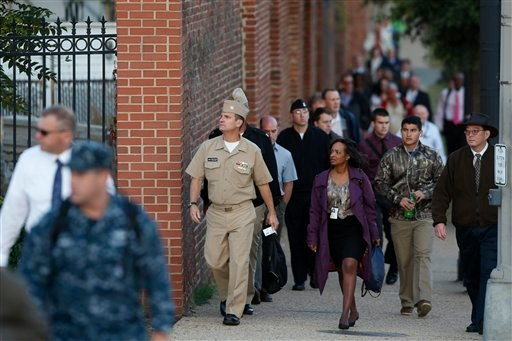 Military personnel and workers walk along the perimeter of the Washington Navy Yard Thursday, Sept. 19, 2013. (AP Photo/Charles Dharapak)