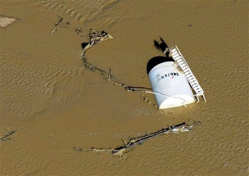 In this Sept. 17, 2013 photo, a crude oil storage tank lies on its side in flood water along the South Platte River, in Weld County, Colo. (AP)