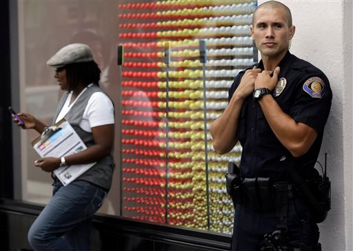 Pasadena Police officer M. Chavarin guards the front of the Apple store in Pasadena, Calif., as customers wait in line for the latest versions of the iPhone during the opening day of sales of the iPhone 5s and iPhone 5C, Friday, Sept. 20, 2013. (AP)