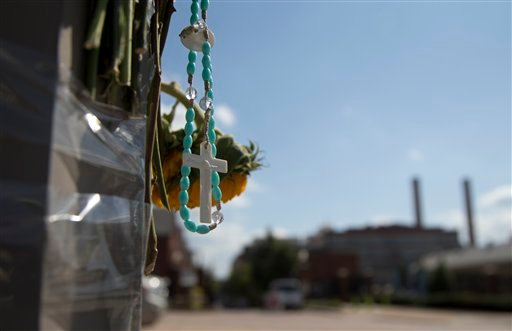 A rosary hangs from a makeshift memorial on a lamp post across the street from the Washington Navy Yard, Friday, Sept. 20, 2013, in Washington.