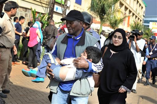 A rescue worker helps a child outside the Westgate Mall in Nairobi, Kenya Saturday, Sept. 21, 2013, after gunmen threw grenades and opened fire during an attack that left multiple dead and dozens wounded.