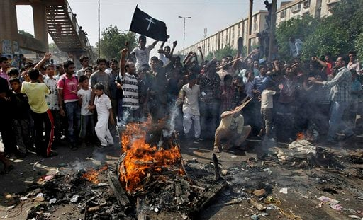 Pakistani Christians chant slogans as they burn materials during a protest against a suicide attack on a church, Sunday, Sept. 22, 2013 in Karachi, Pakistan.