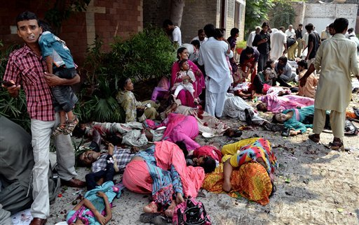 GRAPHIC CONTENT - Pakistanis help victims of a suicide attack at a church in Peshawar, Pakistan, Sunday, Sept. 22, 2013.