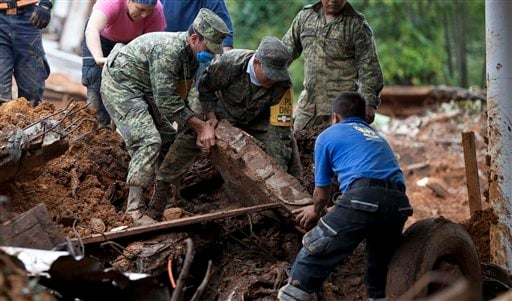Rescue workers and soldiers search for bodies at the site of a landslide in the village of La Pintada, Mexico, Sunday Sept. 22, 2013.