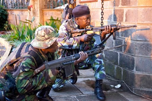 Kenya security personnel take cover outside the Westgate Mall after shooting started inside the mall early Monday morning, Sept. 23, 2013.