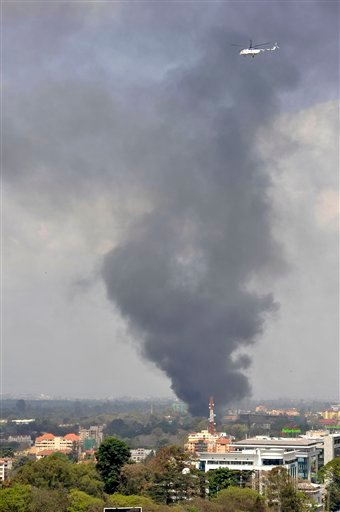 A helicopter flies above as a plume of black smoke billows over the Westgate Mall, following large explosions and heavy gunfire, in Nairobi, Kenya Monday, Sept. 23, 2013.